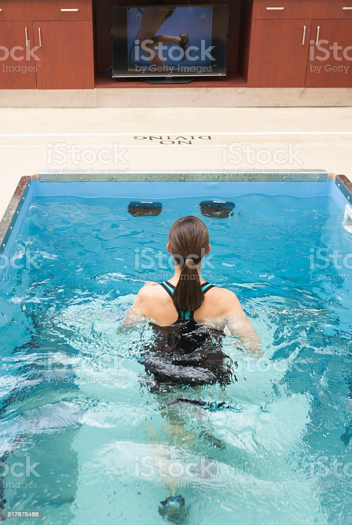 Woman Running In Underwater Treadmill, Hydrotherapy Pool. stock photo