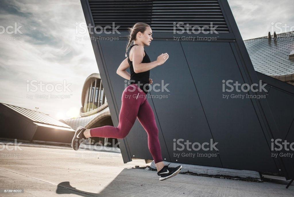 Frau läuft in urbaner Umgebung – Foto