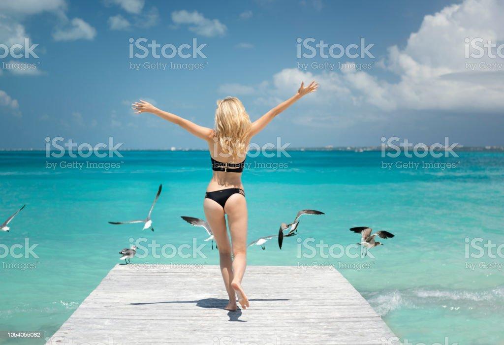 Frau rennt an einem Pier im Urlaub mit Möwen, Cancun, Mexiko – Foto