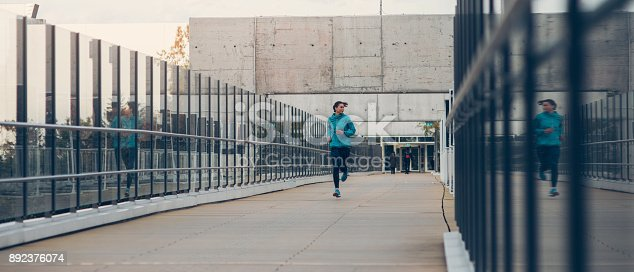 Woman running on a bridge in the city.