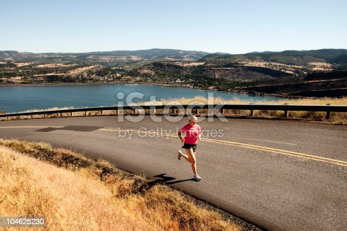 A woman jogging along a beautiful section of road through the Columbia Gorge. The Columbia River is seen below.
