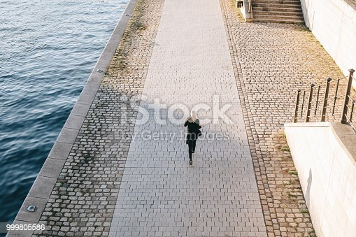 istock Woman running on a sunny evening by the river. 999805586