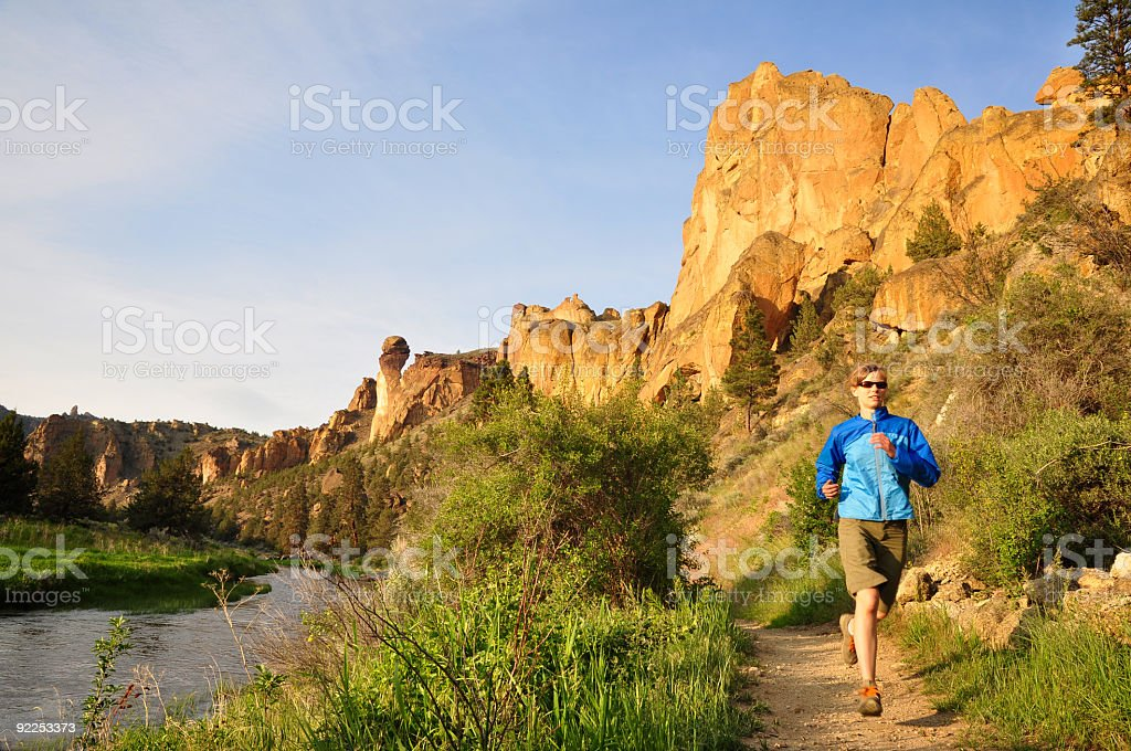 A woman running on a trail in the daylight royalty-free stock photo