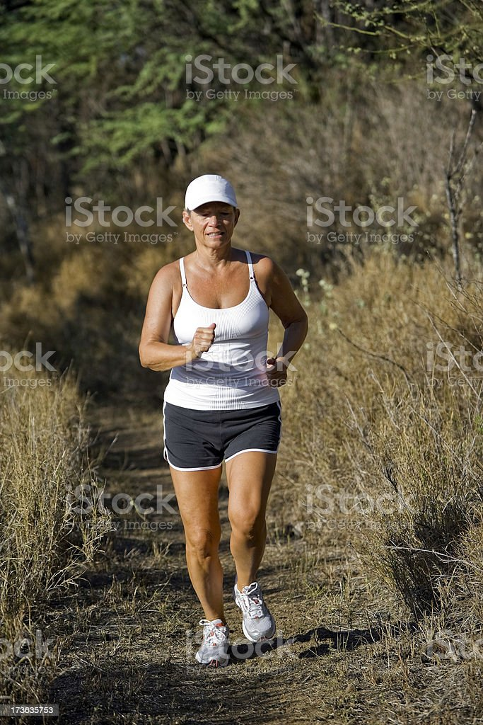 Woman running on a trail royalty-free stock photo