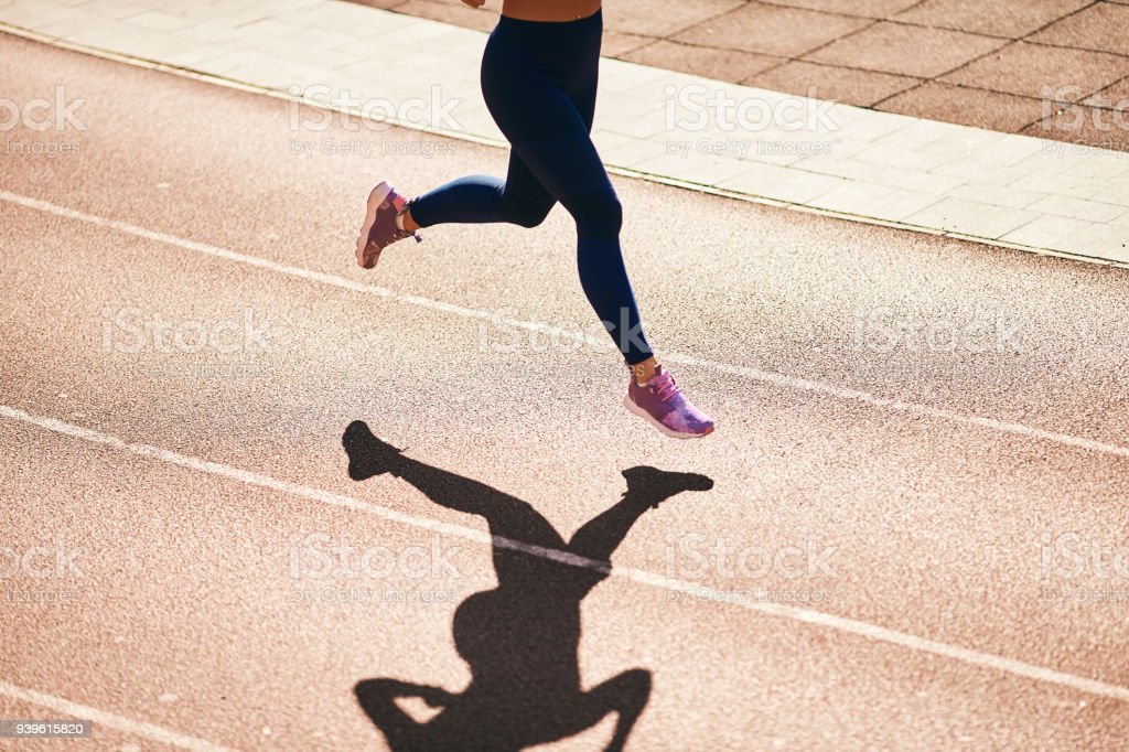 woman running on atlethic track. stock photo