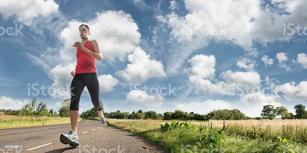Woman Running on Country Road stock photo