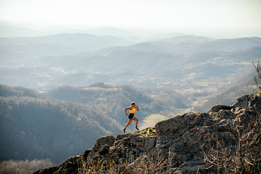 Woman athlete trail runner running and climbing mountain cliff during her training. Extreme terrain.