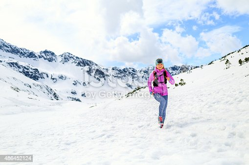 484750230 istock photo Woman running on snow in mountains in inspirational winter landscape 486452124