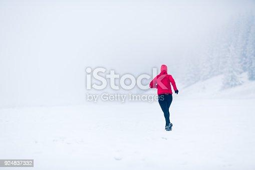 484750230 istock photo Woman running on snow in winter mountains 924837332
