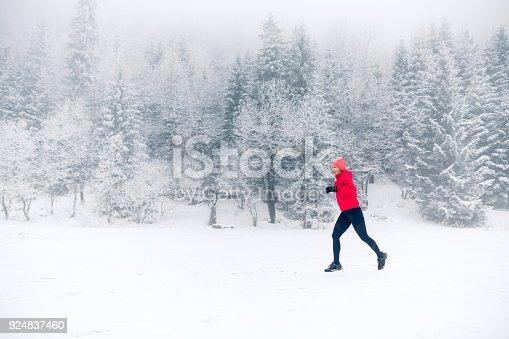 484750230 istock photo Woman running on snow in winter mountains 924837460