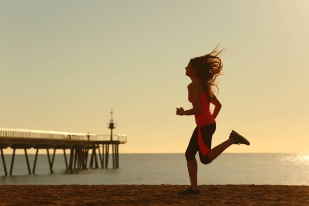 frau läuft am strand bei sonnenaufgang - gewicht schnell verlieren stock-fotos und bilder