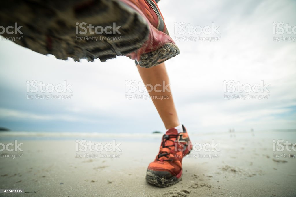 Woman running on the beach-Close up on shoes stock photo