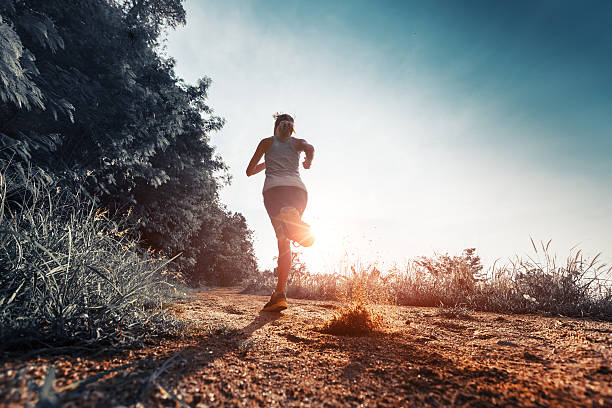 Woman running on the road Young woman running on the gravel road at sunset wet clothing women t shirt stock pictures, royalty-free photos & images