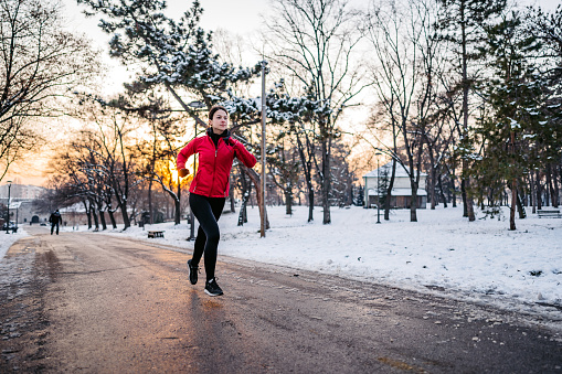 Young athlete woman running down a path on winter day in public park.