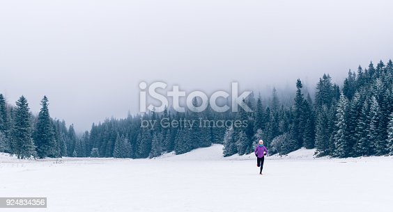 484750230 istock photo Woman running on winter trail in forest, fitness inspiration 924834356