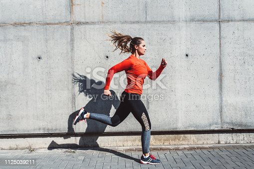 Woman in jogging outfit running outdoors.