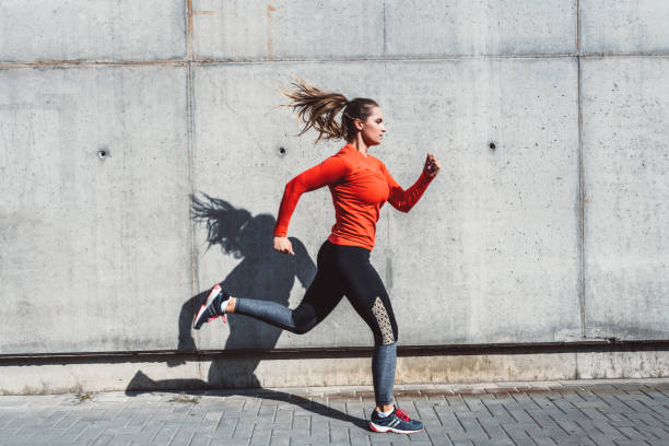 Woman running outdoors in the city stock photo