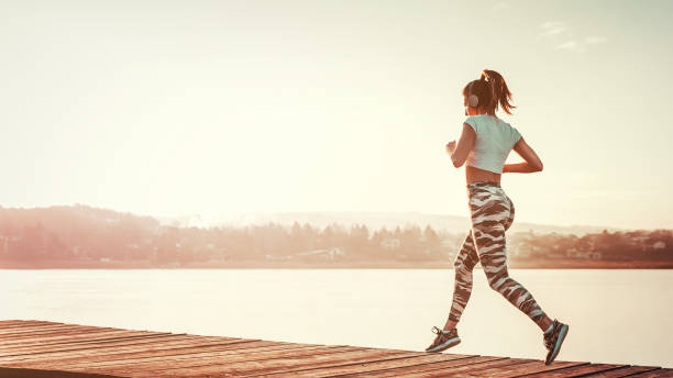 Woman running outdoors on sunny day by the water stock photo