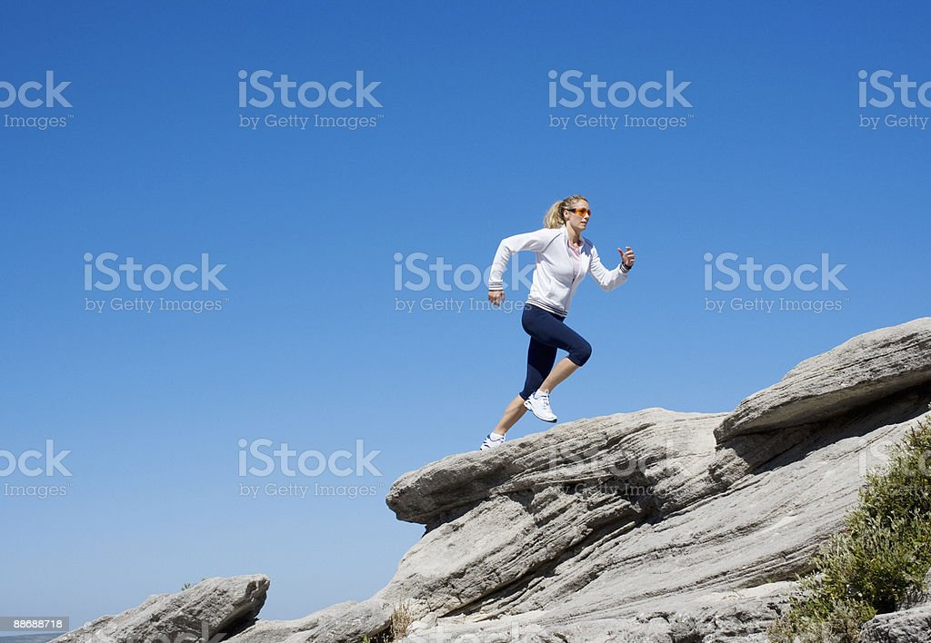 Woman running over rocks royalty-free stock photo