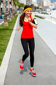 Young smiling woman in the red sportswear running on the street in the city