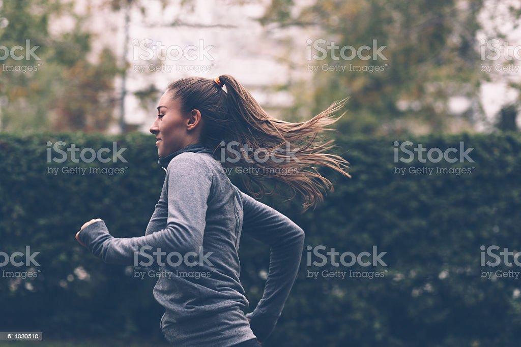 Woman running Woman running. Female runner jogging, training for marathon. Fit girl fitness athlete model exercising outdoor. Activity Stock Photo
