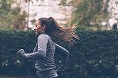 Woman running. Female runner jogging, training for marathon. Fit girl fitness athlete model exercising outdoor.