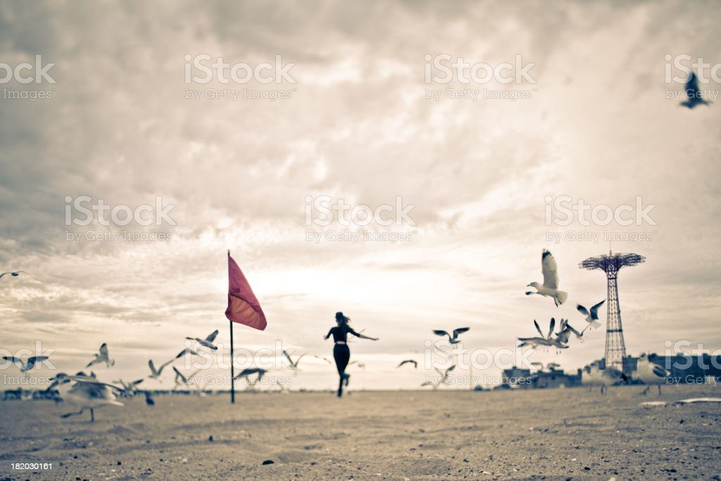 Woman running through a flock of seagulls stock photo