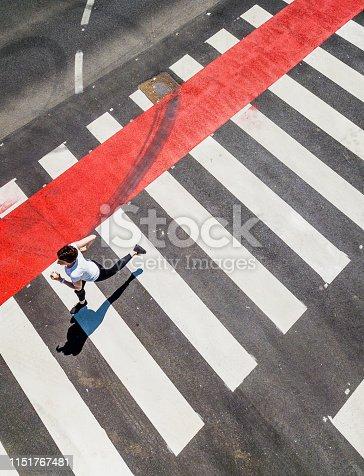 Woman Running Through a Zebra Crossing