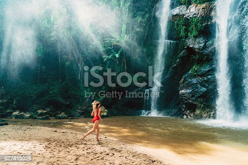 Young Caucasian woman running to  the tropical waterfall in Thailand