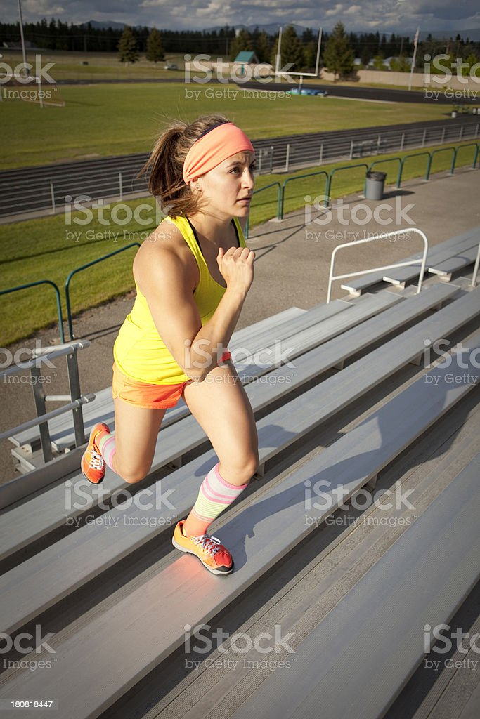 Woman running up bleachers during a workout royalty-free stock photo