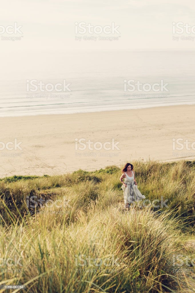 Woman running up Sand dunes in a flowing dress. stock photo