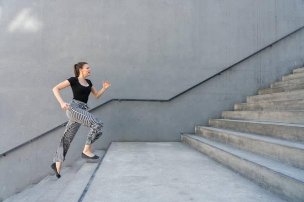 femme monter les marches dans un cadre urbain - marches marches et escaliers photos et images de collection