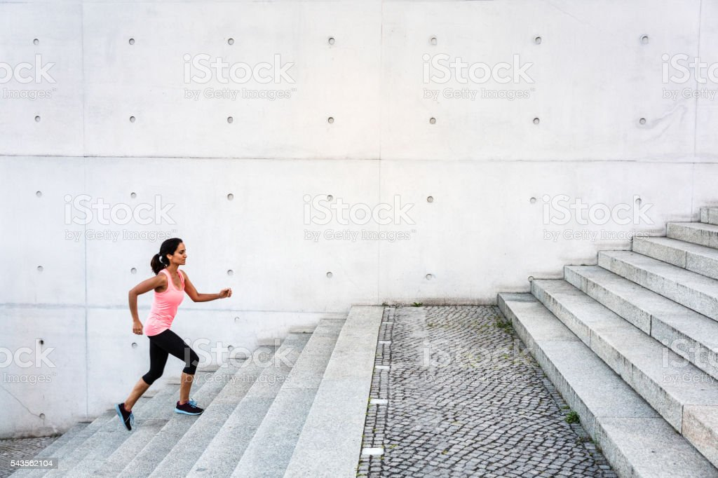 Woman running up steps in urban setting stock photo