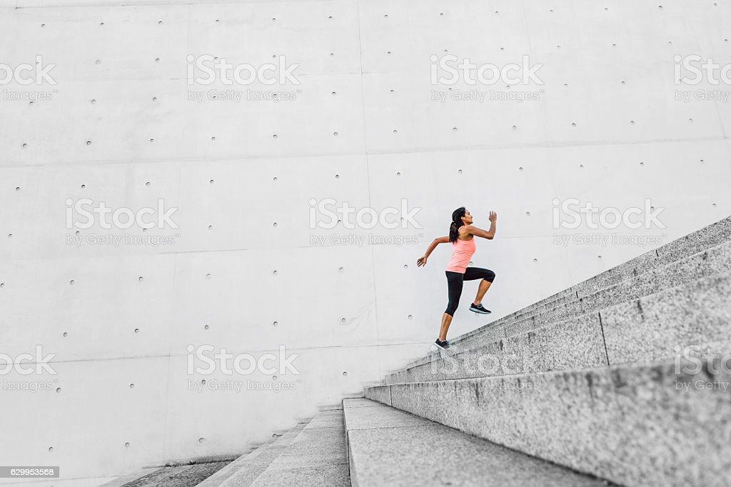 Kobieta działa na schodach w miejskim krajobrazem – zdjęcie