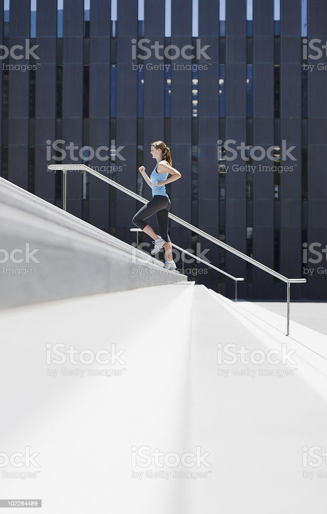 Woman running up urban staircase royalty-free stock photo