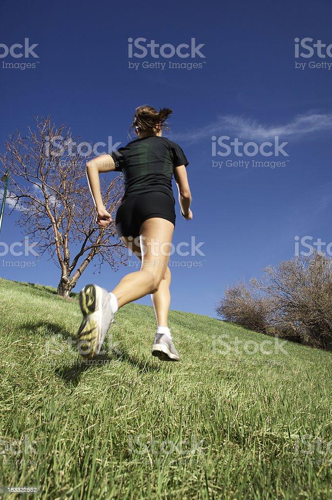Woman running uphill stock photo