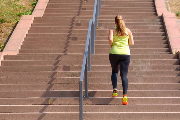 Woman running while climbing stairs during workout Full length rear view of an active and determined middle-aged woman running while climbing stairs during intense workout for weight loss outdoors in a sunny day adipose cell stock pictures, royalty-free photos & images