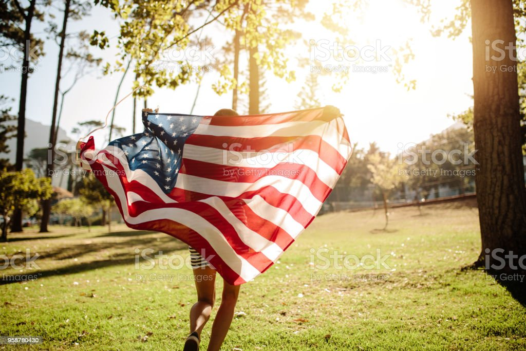 Woman running with american flag in park stock photo