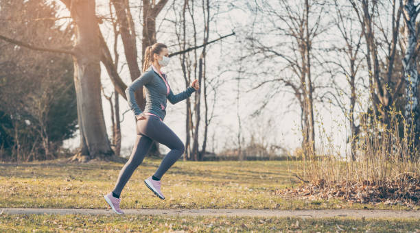 Woman running with face mask to stay healthy during covid-19 stock photo