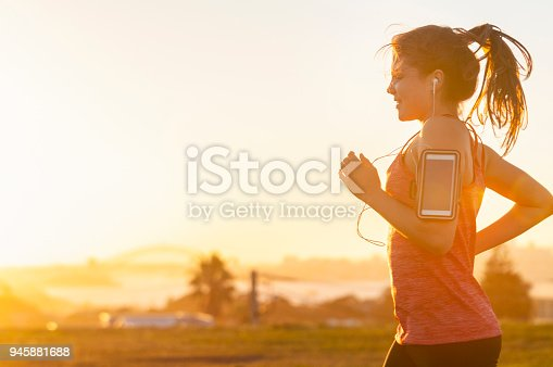 Woman running with mobile phone on her arm. She is exercising at sunset or sunrise with the city of Sydney in the background. She has a smart phone on her arm and is listening to music. Copy space. She is smiling and happy.