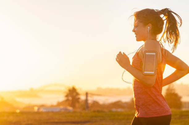 Woman running with mobile phone on her arm. - foto stock