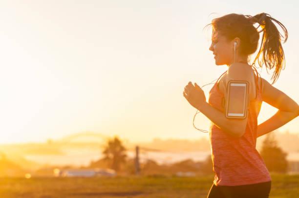 Frau rennt mit Handy auf dem Arm. – Foto