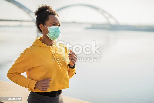 Mid adult African American woman running in the city next to the river and wearing a protective face mask. Corona Virus Outbreak.