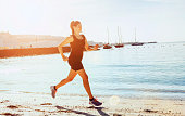 Sporty female runs on a beach near the sea in a tropical climate while the sun shines. Her exercising is pushing her endurance for marathon running or a triathlon. She looks calm, as she runs in the heat.