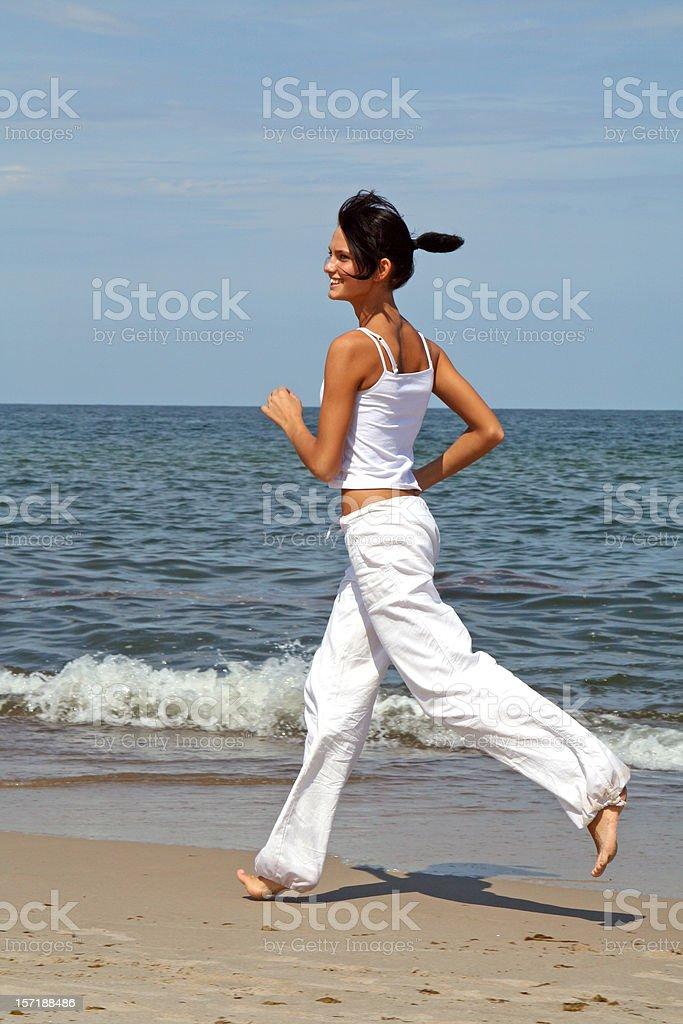 Woman runs on a beach royalty-free stock photo