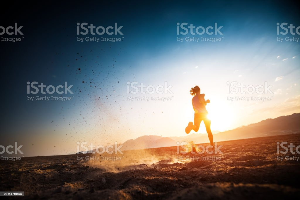 Woman runs on the desert stock photo