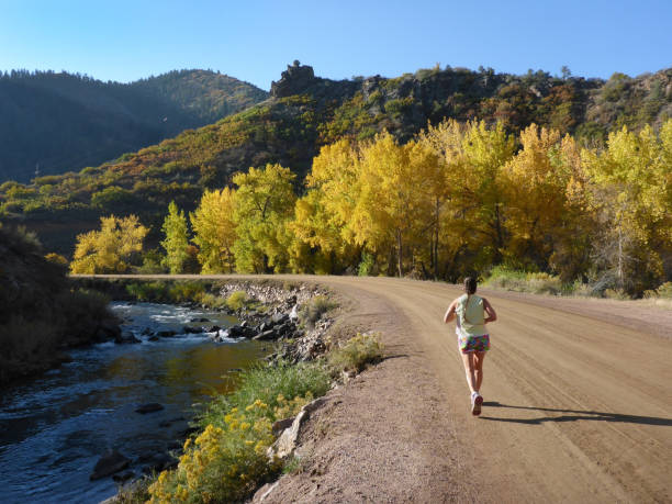 Running along the South Platte River on a dirt road, a woman with a ponytail and shorts enjoys the fall colors and cool temperatures in the Colorado Rocky Mountains.