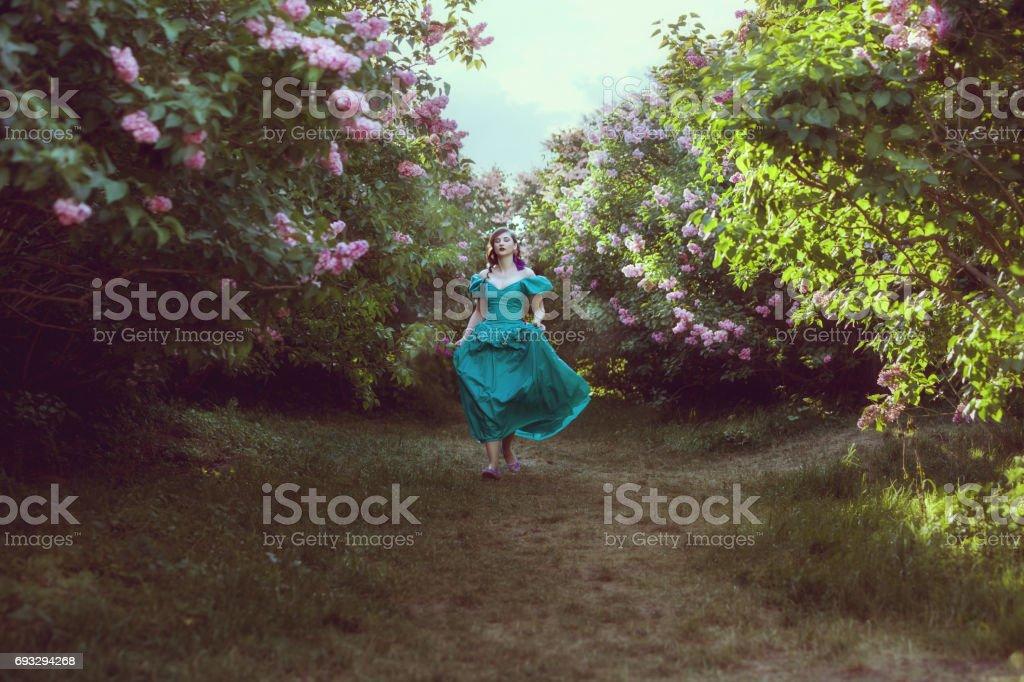 Woman runs through the garden. stock photo