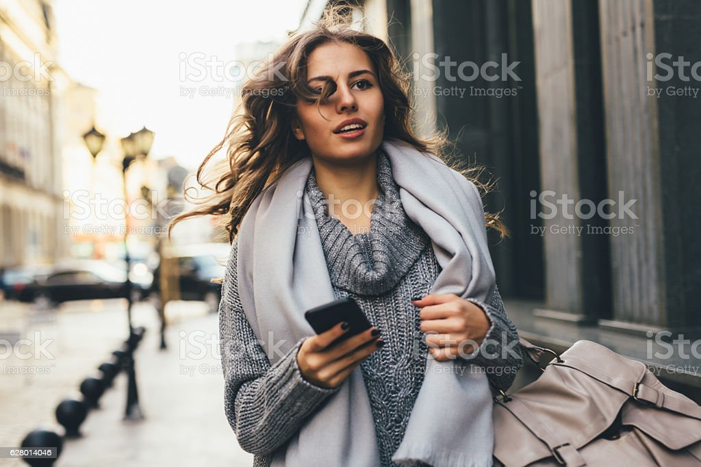Woman rushing down the street stock photo