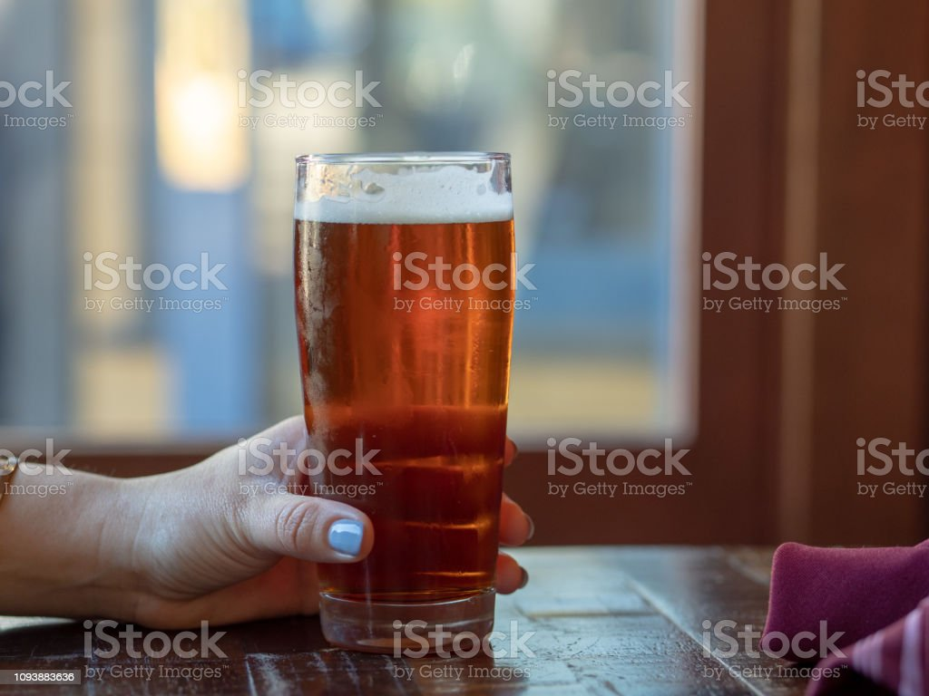 Woman s hand with pink fingernails gripping an amber beer glass in front of window – zdjęcie